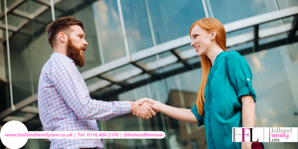 Man and woman shake hands following a family mediation session.